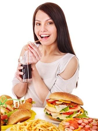 donna in gravidanza che mangia cibo fritto